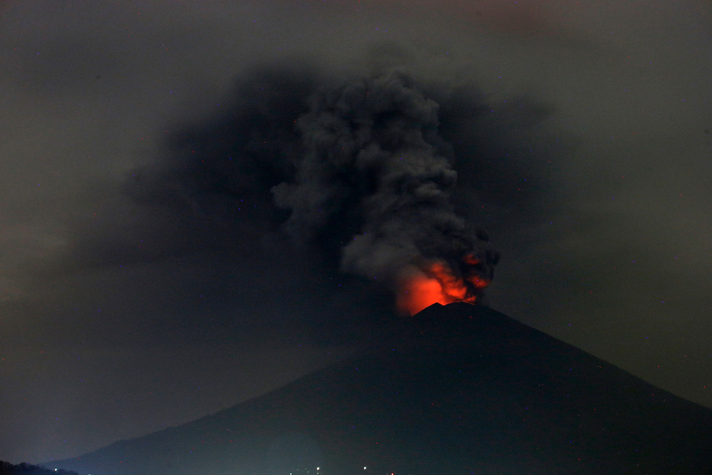 . A view of Mount Agung volcano erupting in Karangasem, Bali, Indonesia, Monday, Nov. 27, 2017. Indonesia authorities raised the alert for the rumbling volcano to highest level on Monday and closed the international airport on tourist island of Bali stranding thousands of travelers. (AP Photo/Firdia Lisnawati)