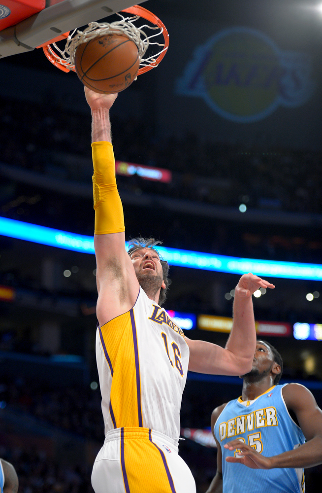 Description of . Los Angeles Lakers forward Pau Gasol, of Spain, dunks as Denver Nuggets forward Kenneth Faried looks on during the first half of their NBA basketball game, Sunday, Jan. 6, 2013, in Los Angeles. (AP Photo/Mark J. Terrill)