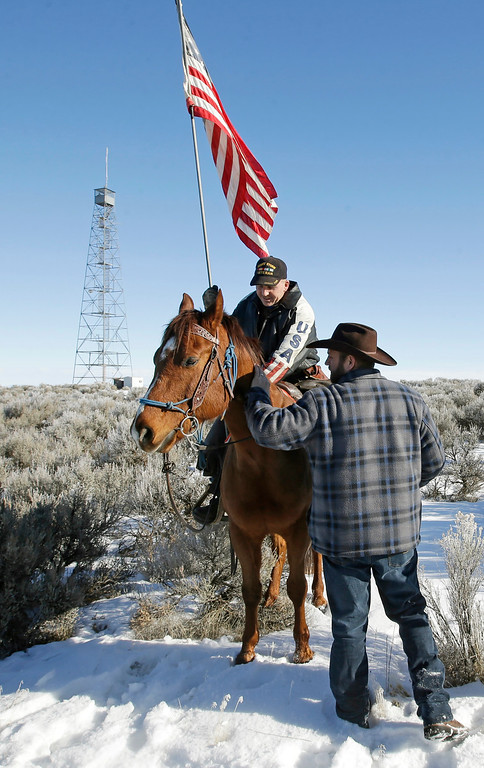. Ammon Bundy, right, is greeted by supporter Dwane Ehmer, of Irrigon Ore., at Malheur National Wildlife Refuge following a news conference Friday, Jan. 8, 2016, near Burns, Ore. Bundy, the leader of a small, armed group occupying the national wildlife refuge in Oregon says the activists have no immediate plans to leave. Bundy spoke to reporters Friday, a day after meeting with a local sheriff who asked the group to go. (AP Photo/Rick Bowmer)
