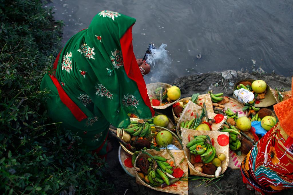 . A Nepalese woman performs rituals on the banks of the Bagmati River during Chhath puja festival in Katmandu, Nepal, Monday, Nov. 8, 2013. (AP Photo/Niranjan Shrestha)