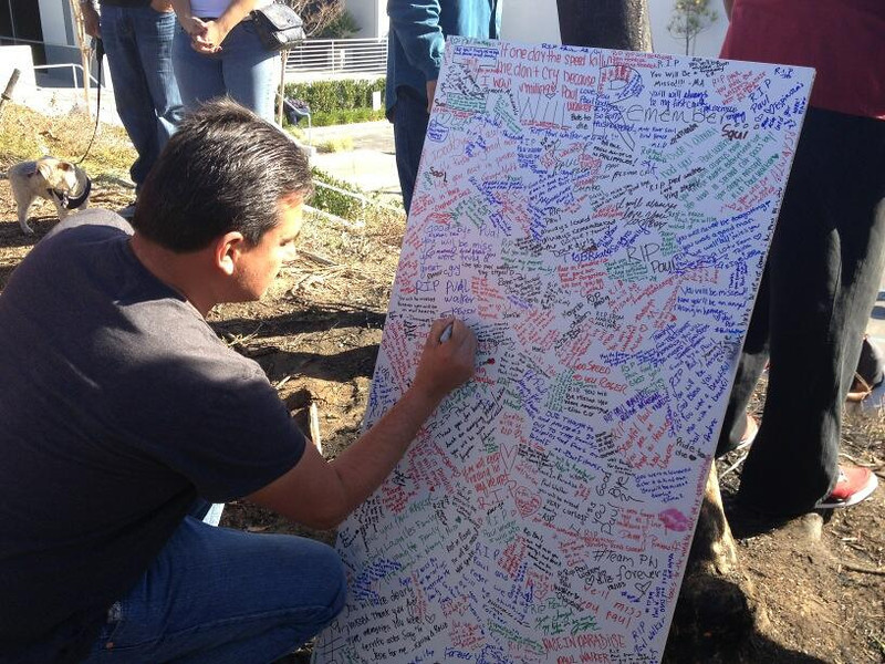 . A man signs a memorial board on Dec. 1, 2013, for Paul Walker and Roger Rodas. The actor and his business partner died in a Porsche crash on Nov. 30, here in Valencia. (Photo by Brenda Gazzar/Los Angeles Daily News)