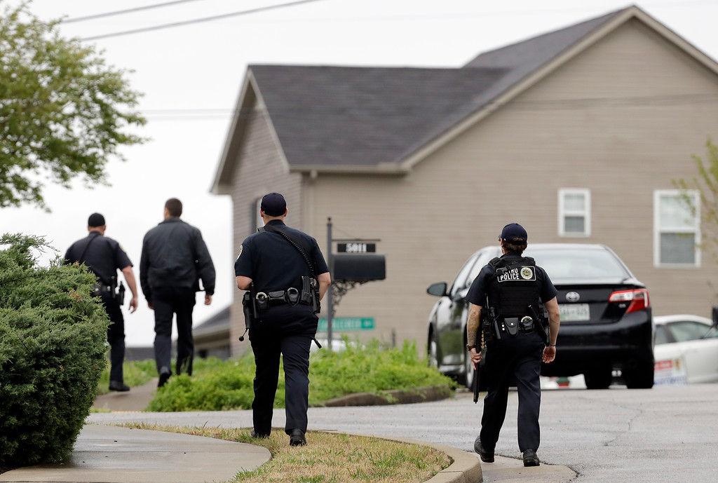 . Nashville police officers search a neighborhood near a Waffle House restaurant Sunday, April 22, 2018, in Nashville, Tenn. At least four people died after a gunman opened fire at the restaurant early Sunday. (AP Photo/Mark Humphrey)
