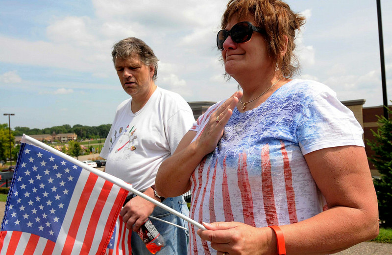 . Nikki Edwards, right, of Edina cries as a long line of police cars stream down Dodd Road in Mendota Heights, on their way to the burial service for officer Patrick Wednesday. With Edwards is her brother Skot Johannsen of Minneapolis.  (Pioneer Press: Scott Takushi)
