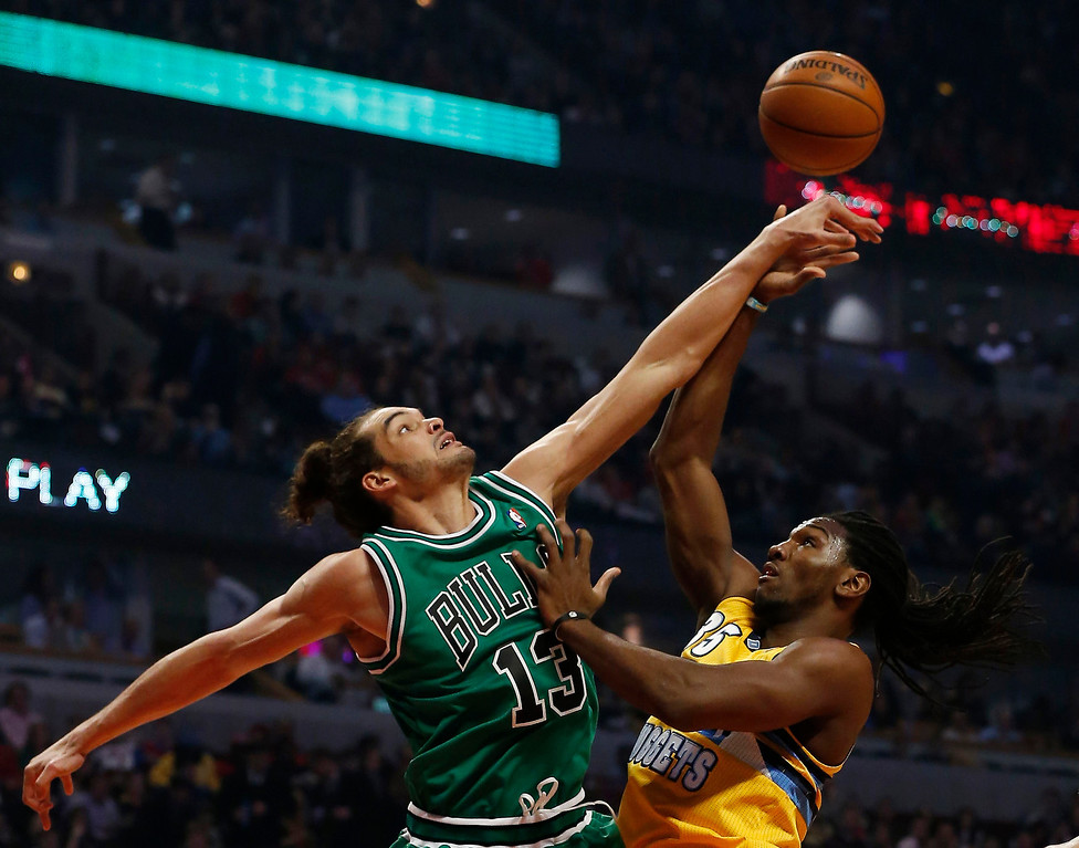 . Chicago Bulls\' Joakim Noah (L) blocks a shot by Denver Nuggets\' Kenneth Faried during the first half of their NBA basketball game in Chicago, Illinois March 18, 2013.   REUTERS/Jim Young