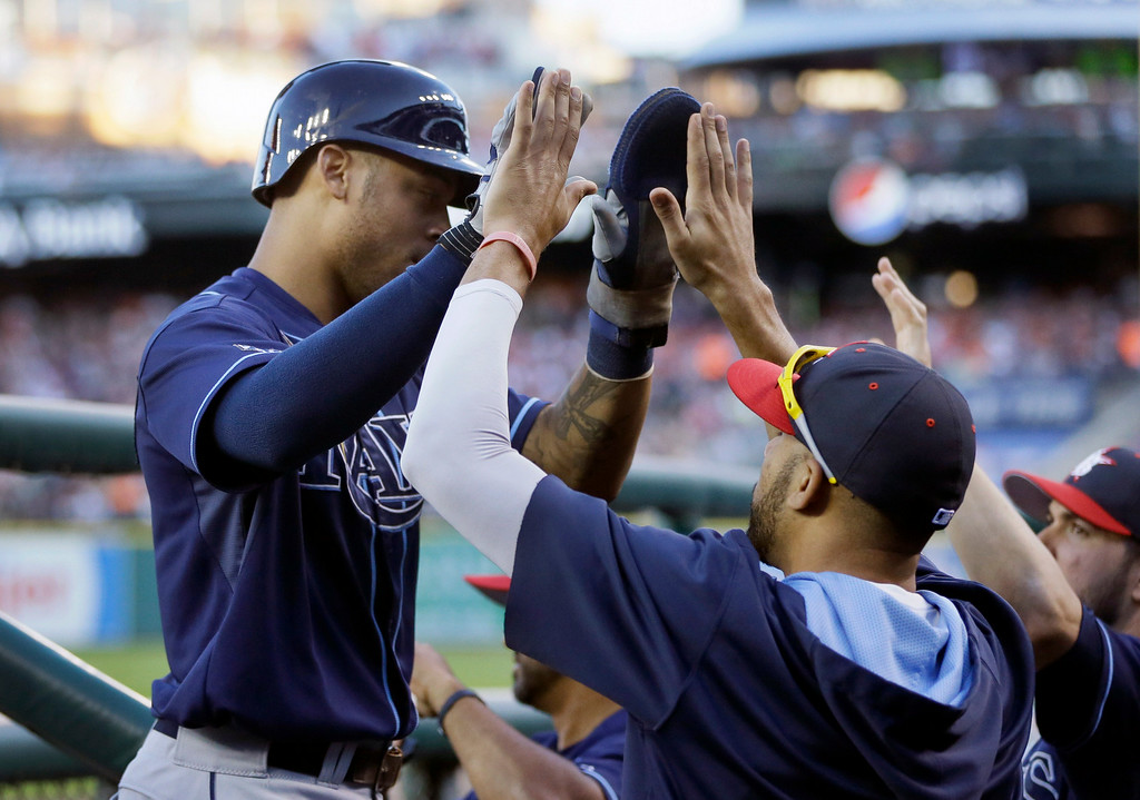 . Tampa Bay Rays\' Desmond Jennings, left, is met in the dugout after scoring from first on a double by teammate Ben Zobrist during the fifth inning of a baseball game against the Detroit Tigers in Detroit, Friday, July 4, 2014. (AP Photo/Carlos Osorio)