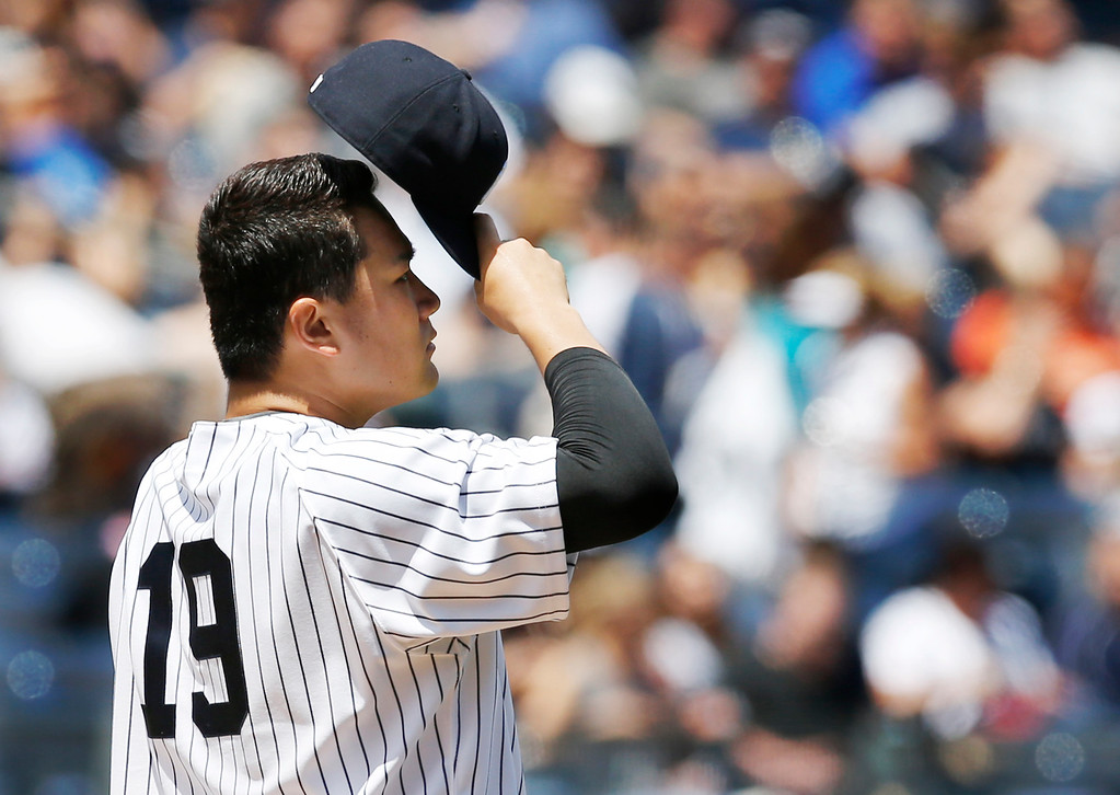 . New York Yankees starting pitcher Masahiro Tanaka (19) removes his cap after a mound conference in the second inning of a baseball game against the Detroit Tigers at Yankee Stadium in New York, Sunday, June 21, 2015. Tanaka allowed six runs in the first two innings, including two, two-run, home runs in the first inning. (AP Photo/Kathy Willens)
