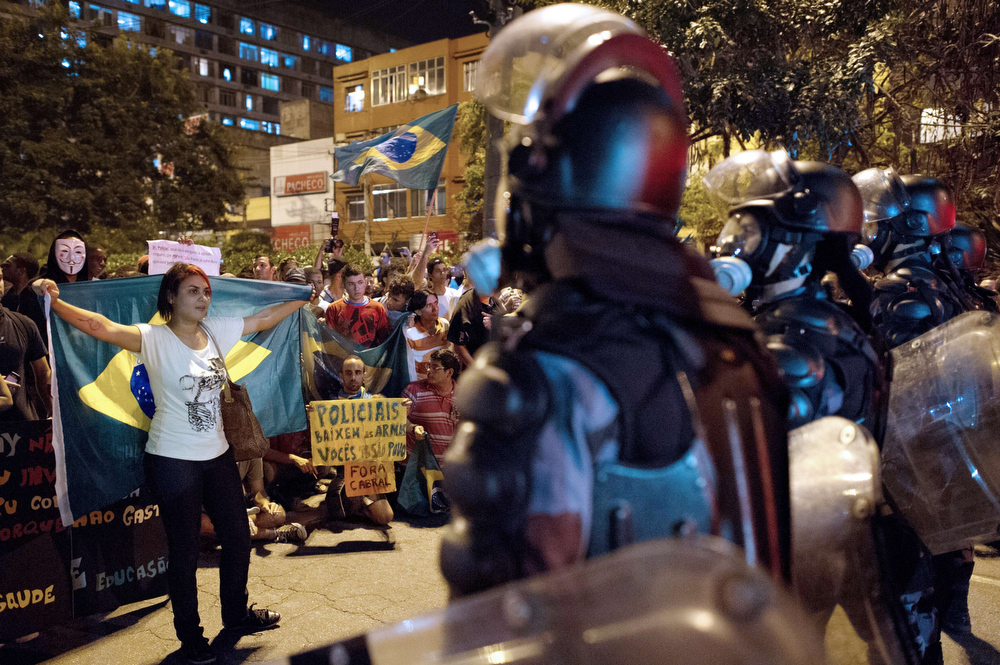 . A demonstrator faces military police from the special unit Chope late on June 19, 2013 in the center of Niteroi, 10 kms from Rio de Janeiro. Protesters battled police late on June 19, even after Brazil\'s two biggest cities rolled back the transit fare hikes that triggered two weeks of nationwide protests.  The fare rollback in Sao Paulo and Rio de Janeiro marked a major victory for the protests, which are the biggest Brazil has seen in two decades.  CHRISTOPHE SIMON/AFP/Getty Images