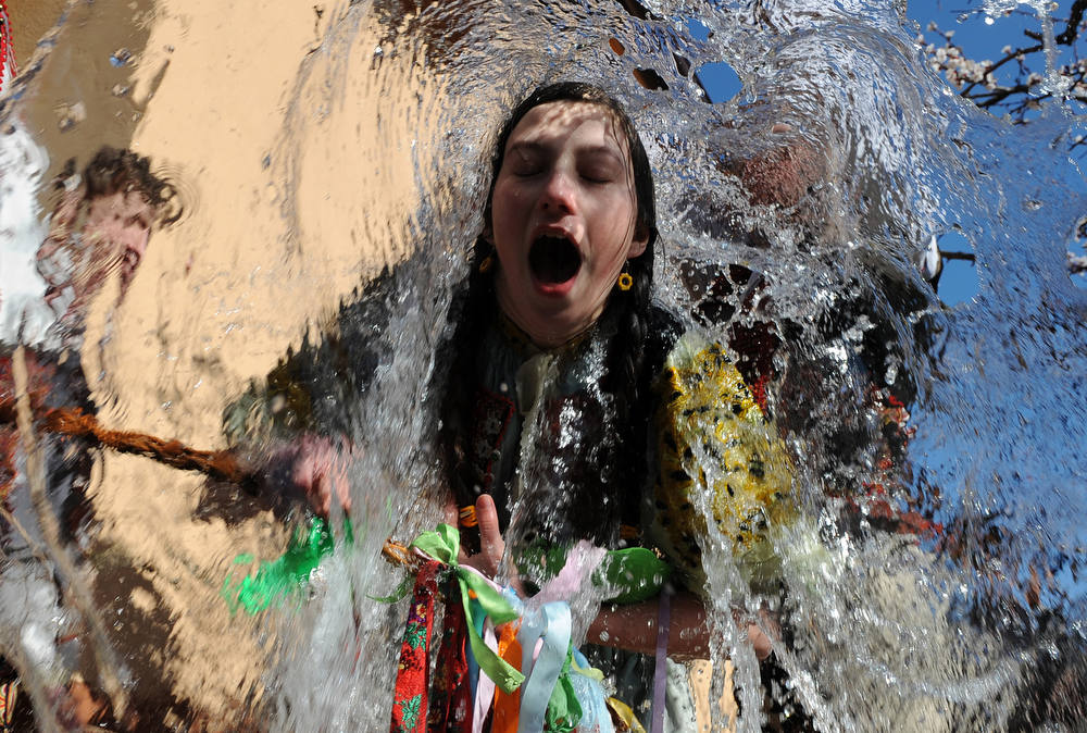 Description of . Young Slovaks dressed in traditional costumes throw a bucket of water at a girl as part of Easter celebrations in the village of Trencianska Tepla, 145 km north of Bratislava on  April 9, 2012. Slovakia's men splash women with water and hit them with a willow to symbolize youth, strength and beauty for the upcoming spring season.AFP PHOTO/SAMUEL KUBANI/AFP/Getty Images