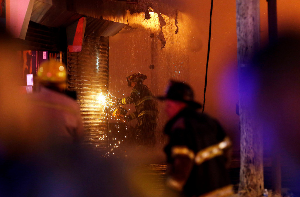 . A firefighter saws through a metal wall on a building while battling a fire at the Seaside Park boardwalk on Thursday, Sept. 12, 2013, in Seaside Park, N.J. The fire began in a frozen custard stand on the Seaside Park section of the boardwalk and quickly spread north into neighboring Seaside Heights. (AP Photo/Julio Cortez)