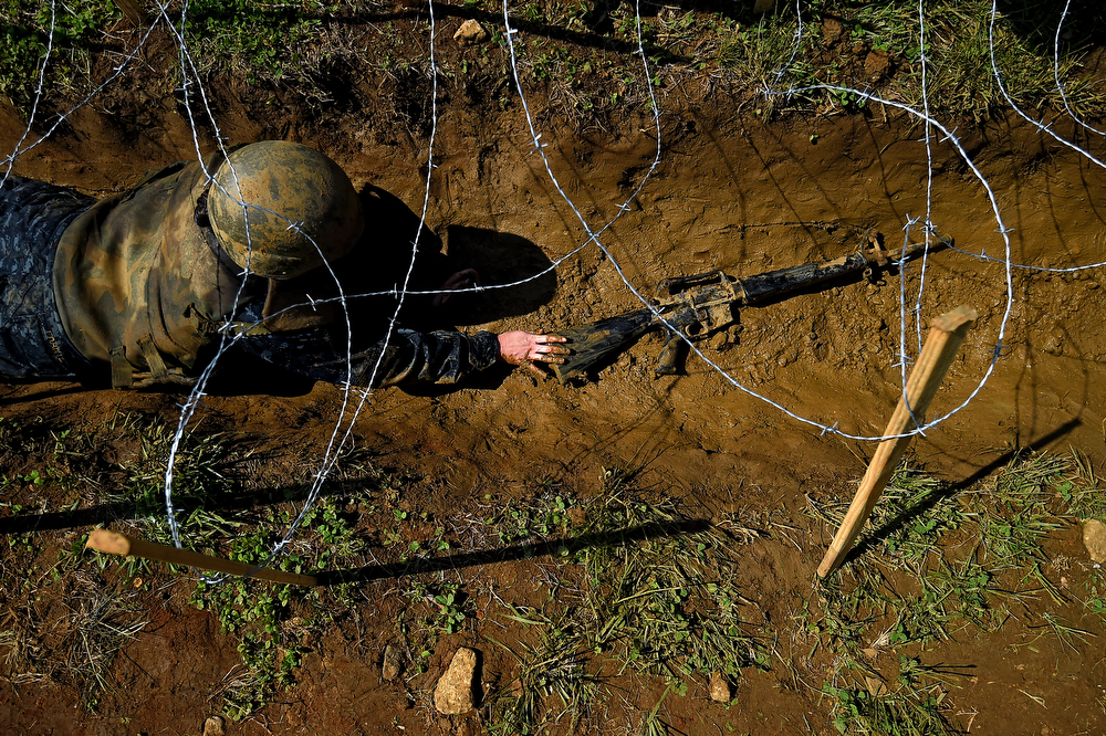 . A member of the United States Naval Academy freshman class pushes a fake-gun through trenches at the wet and sandy station during the annual Sea Trials training exercise at the U.S. Naval Academy on May 13, 2014 in Annapolis, Maryland. (Photo by Patrick Smith/Getty Images)