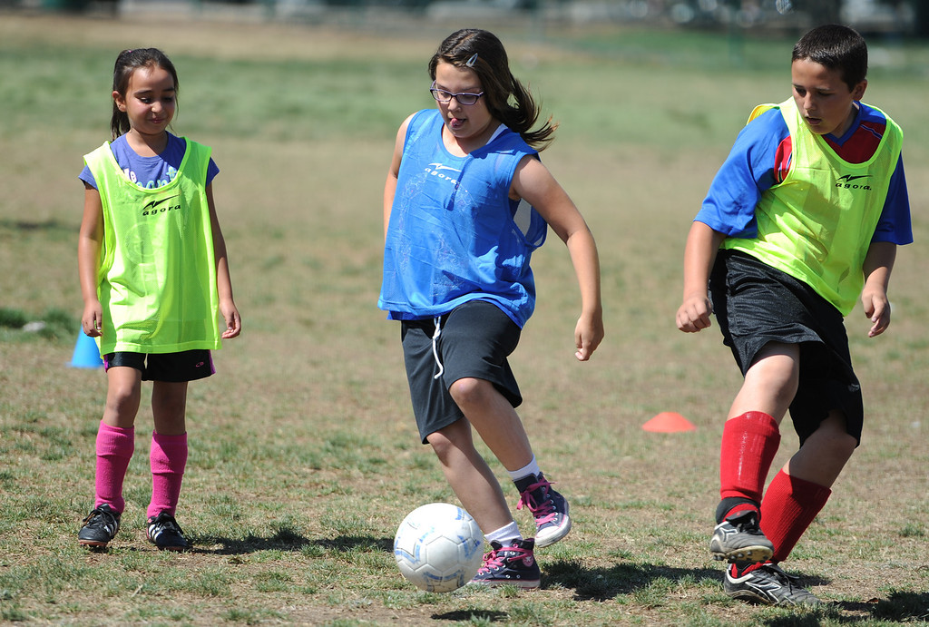 ". Caitlyn Burnett, center, kicks the ball between Heidi Reyes and Jacob Eskelin. In honor of the AYSO\'s 50th anniversary as the nation�s most active and open youth soccer organization, kids at Balboa Park in Encino will join efforts around the country Saturday--over 500,000 players,125,000 volunteers,100 community-based events and a national soccer festival--to set a world record for the ""largest pickup game on Earth.\"" Encino, CA. 5/3/2014(Photo by John McCoy / Los Angeles Daily News)"