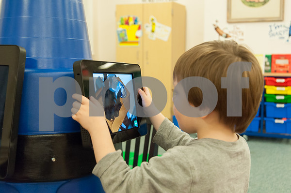12/11/17 Wesley Bunnell | Staff Joshua Madore, age 3 1/2, plays an educational game on one of the iPad stations shaped like a crayon at the Bristol Public Library on Monday evening.
