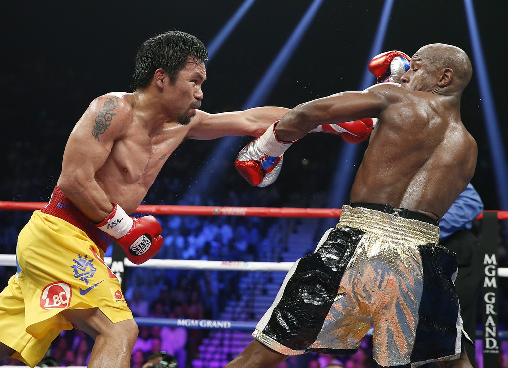 . Floyd Mayweather Jr., right, pulls away from a punch thrown by Manny Pacquiao, from the Philippines, during their welterweight title fight on Saturday, May 2, 2015 in Las Vegas. (AP Photo/John Locher)