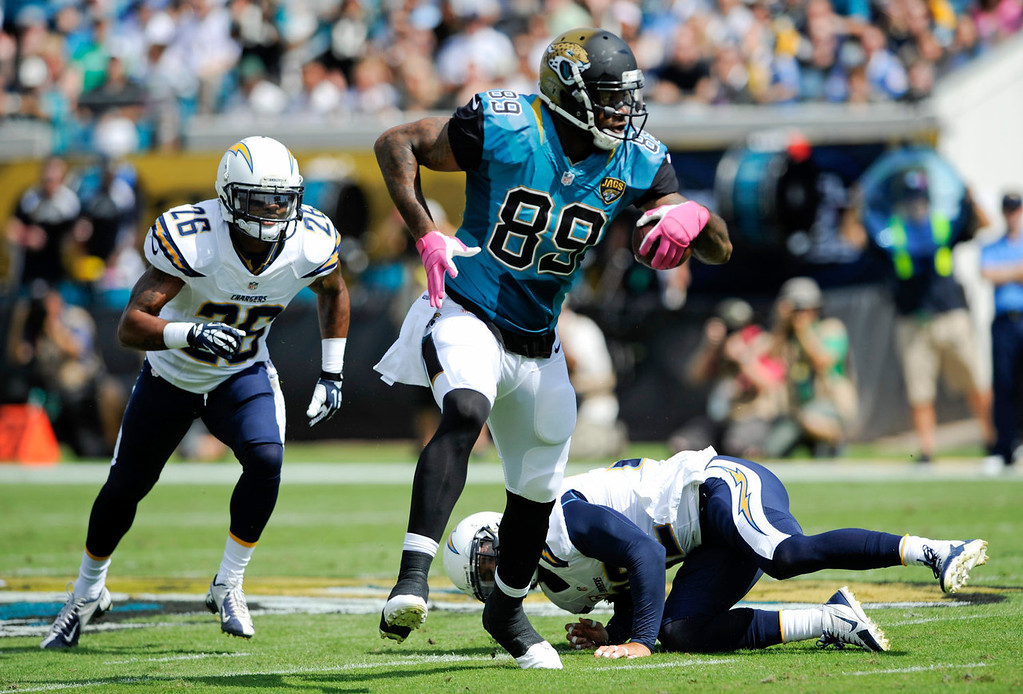. Jacksonville Jaguars tight end Marcedes Lewis (89) runs for yardage after a reception past San Diego Chargers free safety Eric Weddle, lower right, and cornerback Johnny Patrick (26) during the first half of an NFL football game in Jacksonville, Fla., Sunday, Oct. 20, 2013.(AP Photo/Stephen Morton)