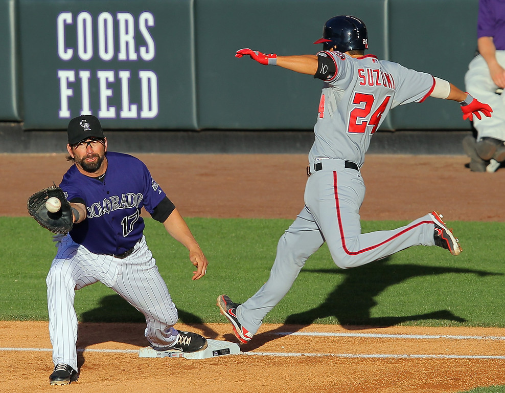 . Kurt Suzuki #24 of the Washington Nationals is safe at first base as first baseman Todd Helton #17 of the Colorado Rockies takes the throw from third baseman Nolan Arenado #28 of the Colorado Rockies in the second inning at Coors Field on June 11, 2013 in Denver, Colorado. Ian Desmond #20 of the Washington Nationals was forced out at third on the play and Suzuki went on to score on a double by Denard Span #2 of the Washington Nationals in the inning.  (Photo by Doug Pensinger/Getty Images)