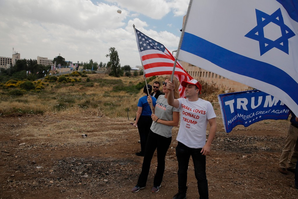 . Israelis hold American and Israeli flags with the new U.S. embassy in the background in Jerusalem, Monday, May 14, 2018. Israel prepared for the festive inauguration of a new U.S. Embassy in contested Jerusalem. (AP Photo/Sebastian Scheiner)
