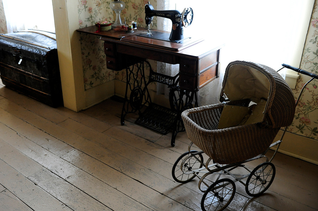 . GOLDEN, CO - MAY 14: A baby carriage and sewing machine sit on display in a room at the Astor House Museum on May 14, 2014, in Golden, Colorado. The museum will soon undergo structural renovations to fix degrading elements of its foundation. While the museum is closed to complete these renovations, exhibits and artifacts will be updated to better reflect its history as a boarding house. (Photo by Anya Semenoff/The Denver Post)