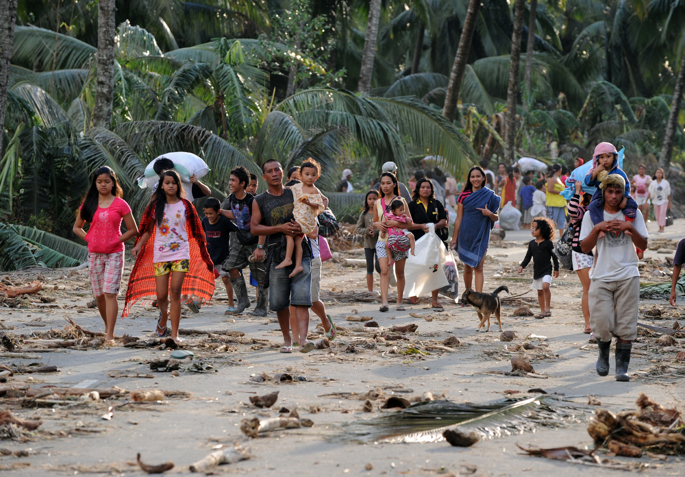 Description of . Residents from a nearby village carry their belongings as they evacuate to a safer place  in the village of Andap, New Bataan town, Compostela Valley province on December 5, 2012, a day after the powerful Typhoon Bopha hit the province. At least 274 people have been killed and hundreds remain missing in the Philippines from the deadliest typhoon to hit the country this year, the civil defence chief said December 5.  TED ALJIBE/AFP/Getty Images
