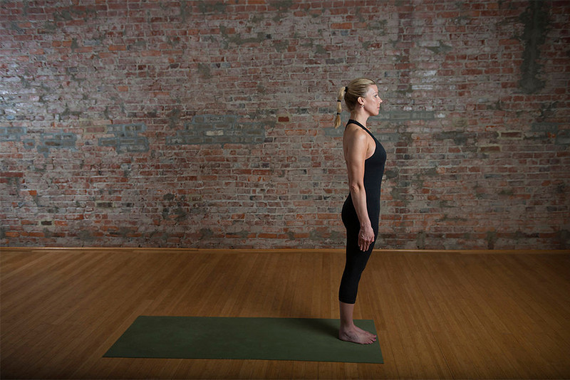 . Yoga instructor Mimi Rieger demonstrates a sun salutation sequence. 1) In mountain pose, stand straight with arms at your side at the front of your mat.  (Photo for The Washington Post by Amanda Voisard.)