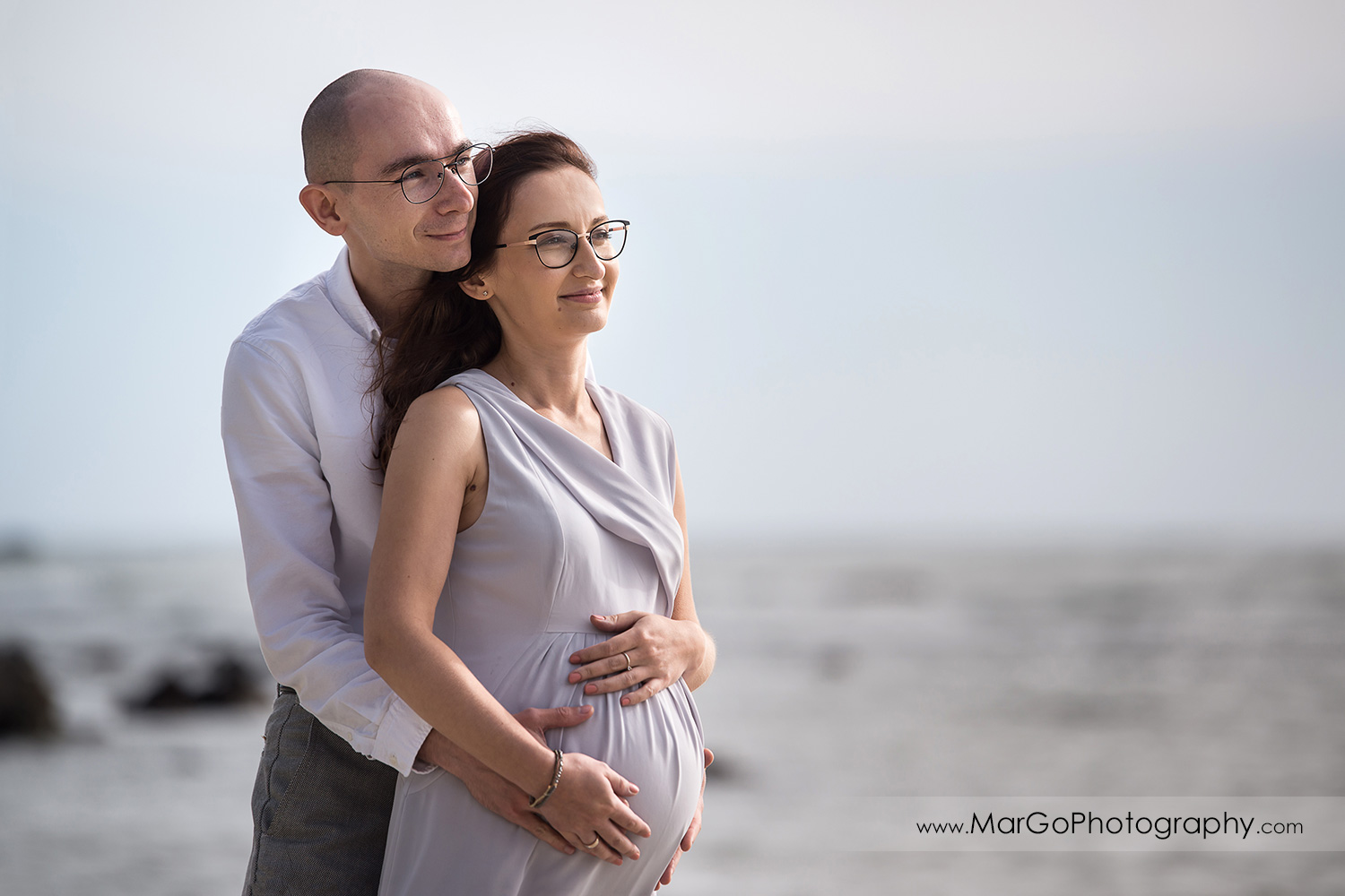 3/4 pose portrait of man and pregnant woman in gray dress on the Moss Beach during maternity session