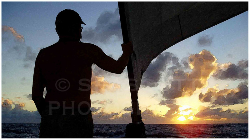 Aboard a yacht bound for the Caribbean from Europe, a crewman watches the sunset through trade wind clouds.