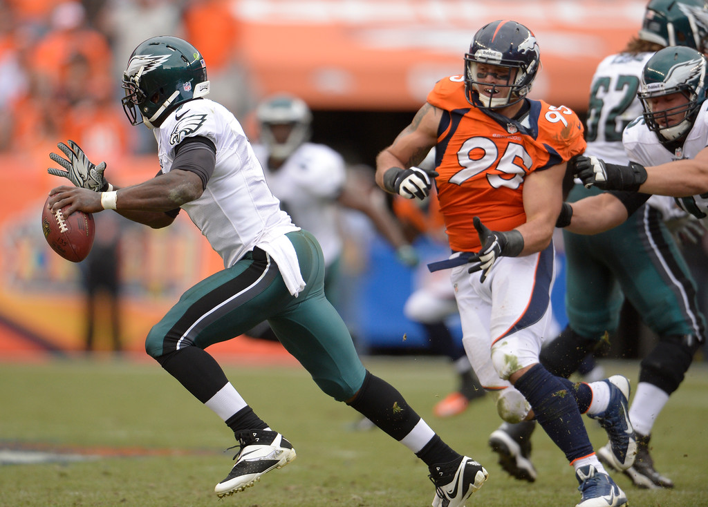 . Philadelphia Eagles quarterback Michael Vick (7) on the run from Denver Broncos defensive end Derek Wolfe (95) during the third quarter.  (Photo by Joe Amon/The Denver Post)