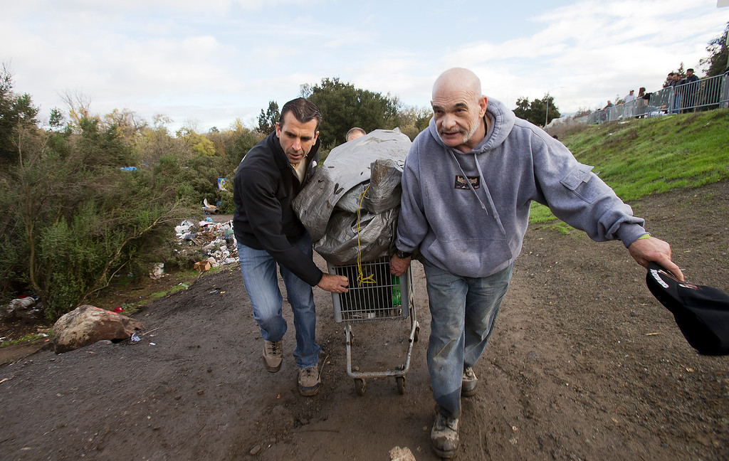 . San Jose Mayor-elect Sam Liccardo, left, helps Andrew Costa, right, a resident of The Jungle, move his possessions out of the homeless encampment in San Jose, Calif., on Thursday, Dec. 4, 2014. (LiPo Ching/Bay Area News Group)