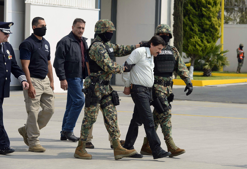 """. Mexican drug trafficker Joaquin Guzman Loera aka \""""el Chapo Guzman\"""" (2-R), is escorted by marines as he is presented to the press on February 22, 2014 in Mexico City. The Sinaloa cartel leader - the most wanted by US and Mexican anti-drug agencies - was arrested early this morning by Mexican marines at a resort in Mazatlan, northern Mexico. (ALFREDO ESTRELLA/AFP/Getty Images)"""
