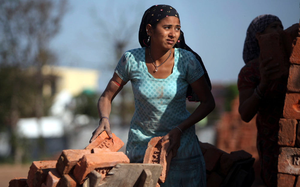 . An Indian woman laborer works at a bricks factory on International Women\'s Day on the outskirts of Jammu, India, Friday, March 8, 2013. (AP Photo/Channi Anand)
