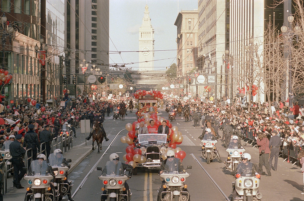 . Thousands of fans line Market Street in San Francisco to greet the San Francisco 49ers during their victory parade after winning the Super Bowl against the Cincinnati Bengals, Jan. 23, 1989.  In the background is the Ferry Building.  In the front car is 49ers coach Bill Walsh, left, and Mayor Art Agnos and 49ers owner Eddie DeBartolo Jr.   (AP Photo/Paul Sakuma)