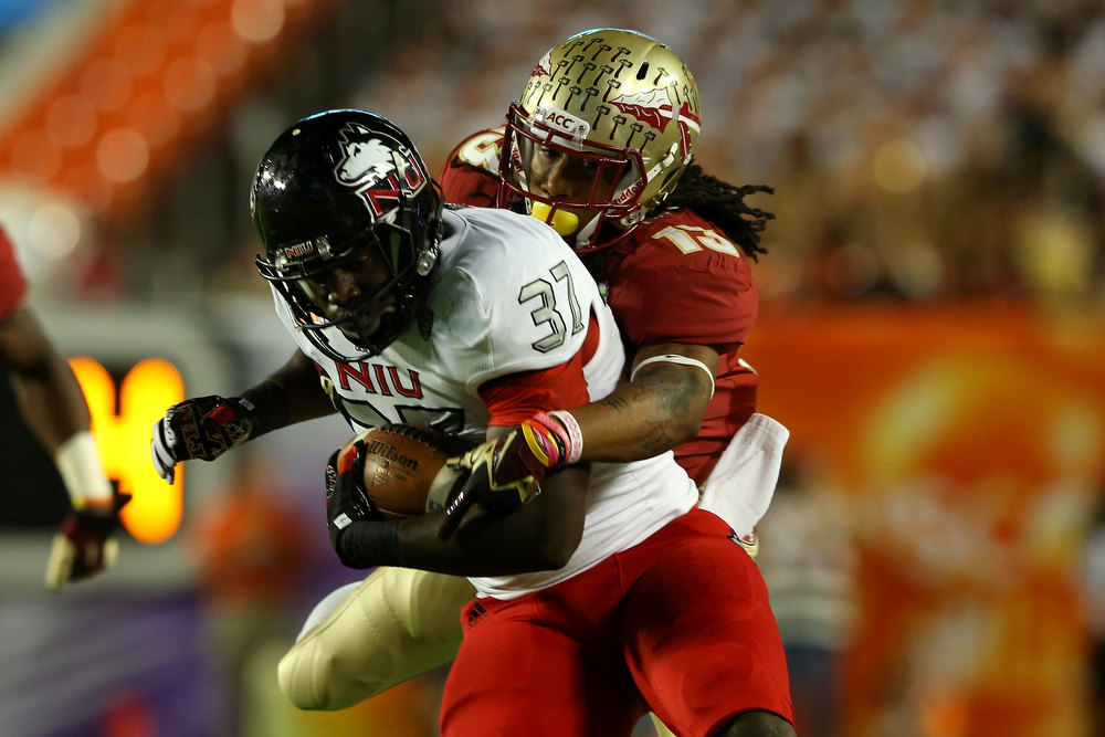 Description of . Desroy Maxwell #37 of the Northern Illinois Huskies runs the ball in the first half against Ronald Darby #13 of the Florida State Seminoles during the Discover Orange Bowl at Sun Life Stadium on January 1, 2013 in Miami Gardens, Florida.  (Photo by Mike Ehrmann/Getty Images)