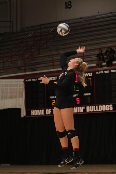 Number 9, Callie Hildebrand, serves the ball.