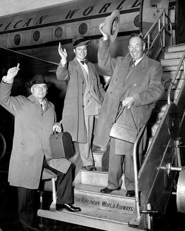 ". 12-30-1949  Wallace Taber (center), outdoors writer for The Denver Post; Ernest Perrine (left), co-owner of the Denver Monitor, and Lud Rettig (right), owner of Denver\'s Save-a-Nickel stores, wave as they \' board a Pan American World Airways Clipper at International airport, New York, on the first leg of their journey to east Africa. They plan to spend two months on the dark continent stalking big game with gun and camera. Taber\'s account of their adventures will appear in The Denver Post in a column. ""African Safari.\"" at a date to be announced later.  Credit: Pan American"