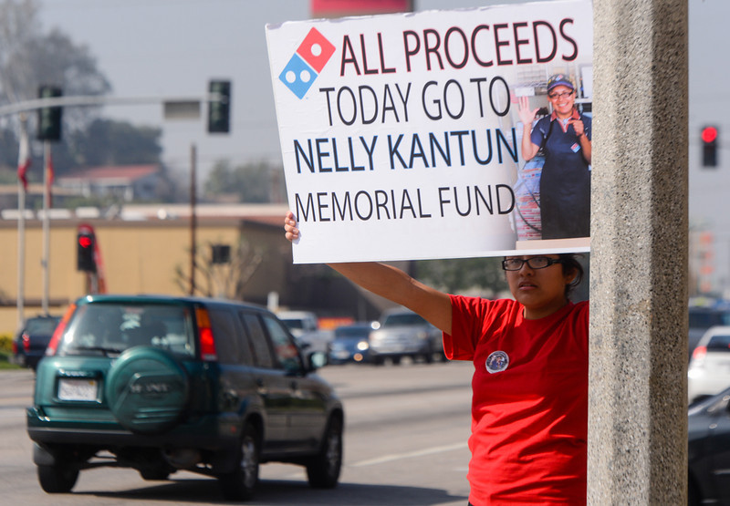 . Cecilia Kantun, niece of slain Domino\'s Pizza manager Nelly Kantun, spreads the word to nearby traffic about an-all-day memorial fundraiser for her aunt at Domino\'s Pizza on Highland Avenue in San Bernardino, CA on Wednesday, Feb. 19, 2014. Kantun, who worked as a Domino\'s employee for more than 20 years, was gunned down at the pizza location on Feb. 12. One-hundred percent of the proceeds earned Wednesday were donated to the memorial fund. (Photo by Rachel Luna / San Bernardino Sun)