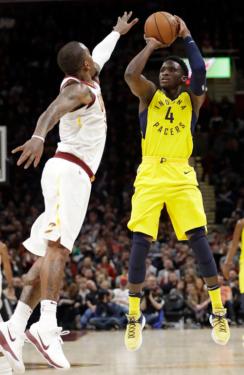 . Indiana Pacers\' Victor Oladipo (4) shoots over Cleveland Cavaliers\' JR Smith (5) in the second half of an NBA basketball game, Friday, Jan. 26, 2018, in Cleveland. (AP Photo/Tony Dejak)