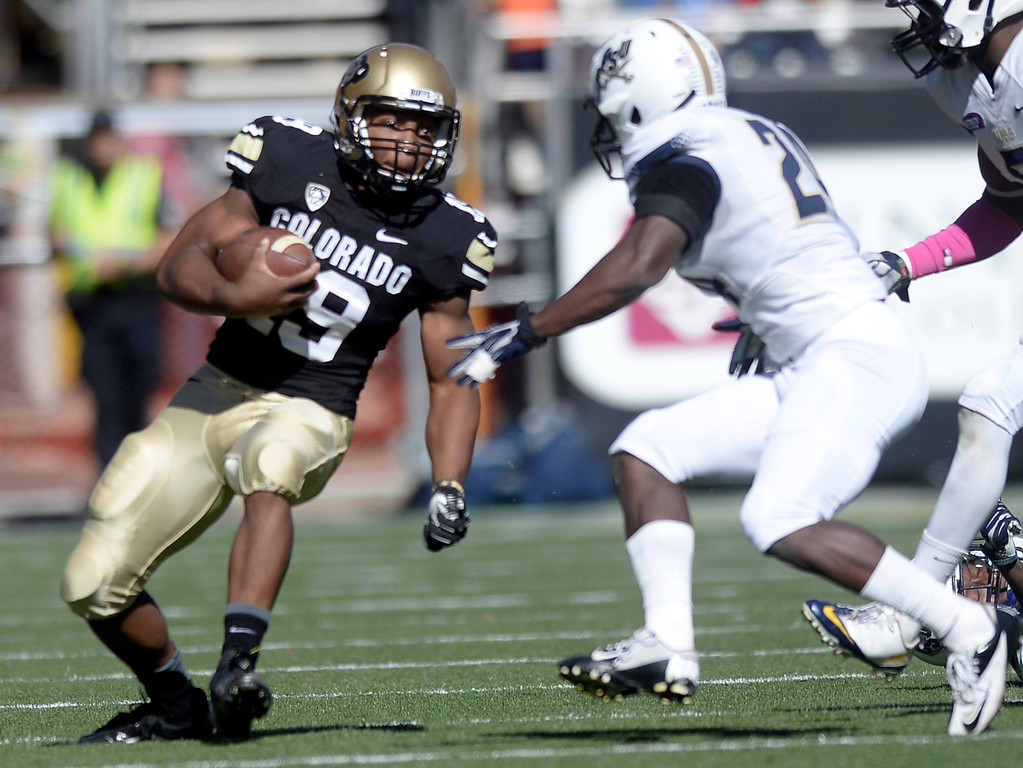 . University of Colorado\'s Michael Adkins II runs the ball before being tackled by Damian Dixon during a game against Charleston Southern on Saturday, Oct. 19, at Folsom Field in Boulder.  (Jeremy Papasso/Boulder Daily Camera)