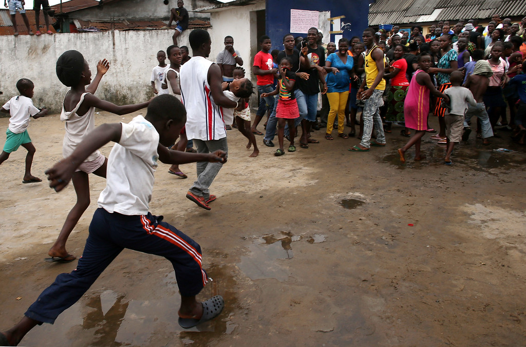 """. A man carries out a girl from an Ebola isolation center as a mob overruns the facility in the West Point slum on August 16, 2014 in Monrovia, Liberia. A crowd of several hundred people, chanting, \""""No Ebola in West Point,\"""" crashed through the gates and took out the patients, many saying that the Ebola epidemic is a hoax. The center, a closed primary school originally built by USAID, was being used by the Liberian Health Ministry to temporarily isolate people suspected of carrying the virus. Some 10 patients had \""""escaped\"""" the building the night before, according to a nurse there, as the center had no medicine to treat them. The Ebola epidemic has killed more than 1,000 people in four West African countries, with Liberia now having the most deaths.  (Photo by John Moore/Getty Images)"""