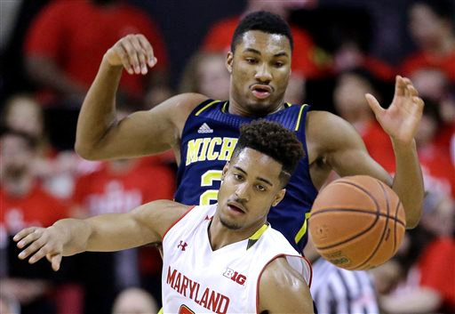 . Maryland guard Melo Trimble, bottom, and Michigan guard/forward Zak Irvin chase after a loose ball during the first half of an NCAA college basketball game, Saturday, Feb. 28, 2015, in College Park, Md. (AP Photo/Patrick Semansky)