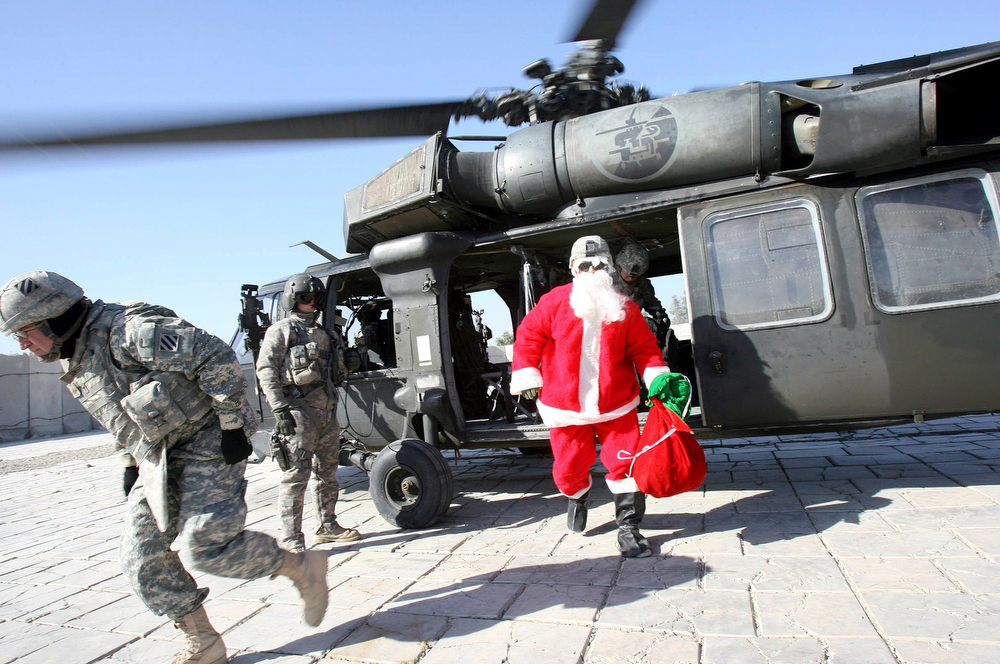 . A US soldier dressed as Santa Claus arrives with a helicopter at the Hammer base in southern Baghdad on Christmas eve, 24 December 2007. Christians around the world will celebrate Christmas tomorrow marking the birth of Jesus Christ. AFP PHOTO / ALI AL-SAADI