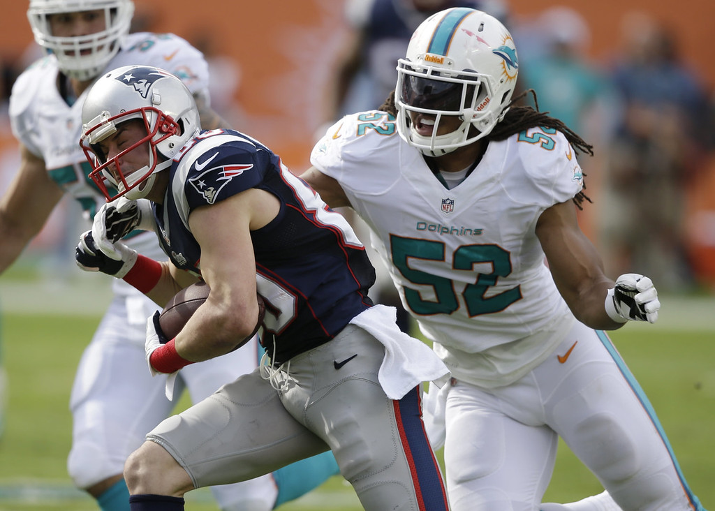 . Miami Dolphins outside linebacker Philip Wheeler (52) attempts to tackle New England Patriots wide receiver Danny Amendola (80) during the first half of an NFL football game on Sunday, Dec. 15, 2013, in Miami Gardens, Fla. (AP Photo/Lynne Sladky)