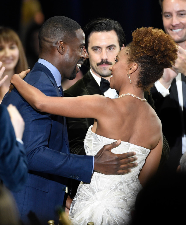 ". Ryan Michelle Bathe, right, congratulates Sterling K. Brown, left, winner of the award for best actor in a drama series for ""This Is Us\"" as co-star Milo Ventimiglia looks on in the audience at the 23rd annual Critics\' Choice Awards at the Barker Hangar on Thursday, Jan. 11, 2018, in Santa Monica, Calif. (Photo by Chris Pizzello/Invision/AP)"