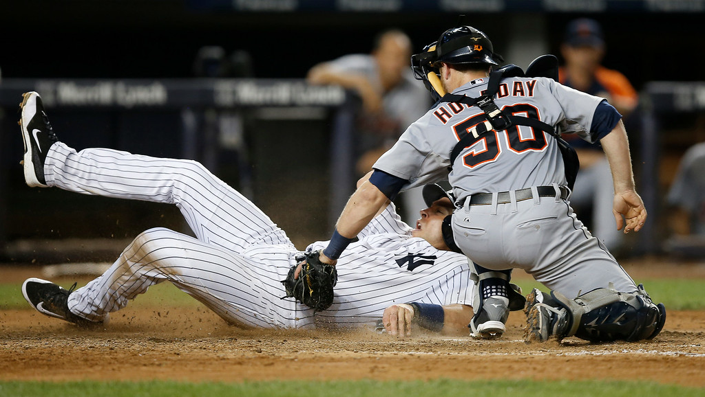 . Detroit Tigers catcher Bryan Holaday (50) applies a tag on New York Yankees Mark Teixeira in the eighth-inning of a baseball game at Yankee Stadium in New York, Wednesday, Aug. 6, 2014.  Teixeira was initially ruled out, but later was ruled safe after a video review. (AP Photo/Kathy Willens)