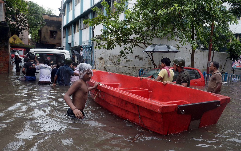 . Indian Police officials pull a boat hrough water-logged streets as others push a police vehicle in Kolkata on October 26, 2013.  Persistent rain for the last 24 hours has thrown normal life in this metropolis out of gear with reports of waterlogging at major arterial roads of the city which received 14 cm rainfall, the highest rainfall during the ongoing depression in eastern India.  Weathermen predicted that the rain, caused due to a depression off Andhra coast over Bay of Bengal, would continue for at least next 24 hours. DIBYANGSHU SARKAR/AFP/Getty Images