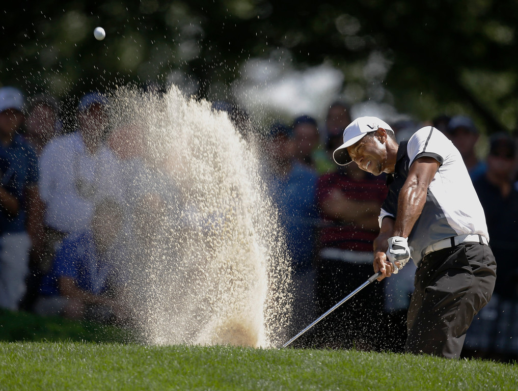 . Tiger Woods hits out of a bunker on the 17th hole during the third round of the PGA Championship golf tournament at Oak Hill Country Club, Saturday, Aug. 10, 2013, in Pittsford, N.Y. (AP Photo/Charlie Neibergall)
