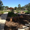 concrete path and log rounds seating with stepping stones in mulch and  post and rail shade structure over bbq table