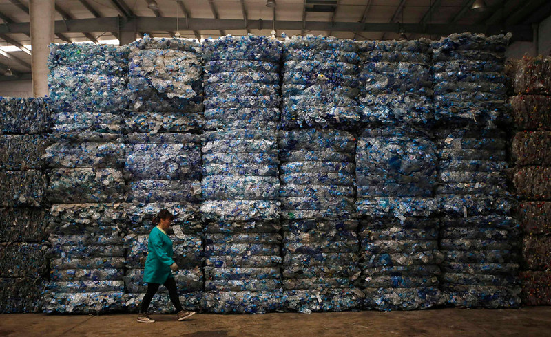 . A worker walks past piles of plastic PET bottles at Asia\'s largest PET plastic recycling factory INCOM Resources Recovery in Beijing May 7, 2013. According to government figures, reported in local media, about 4.67 million tons of recyclable waste was collected in Beijing in 2010. In the same year, 6.35 million tons of trash ended up in landfill in the city. World Environment Day is celebrated annually on June 5. Picture taken May 7, 2013.  REUTERS/Kim Kyung-Hoon