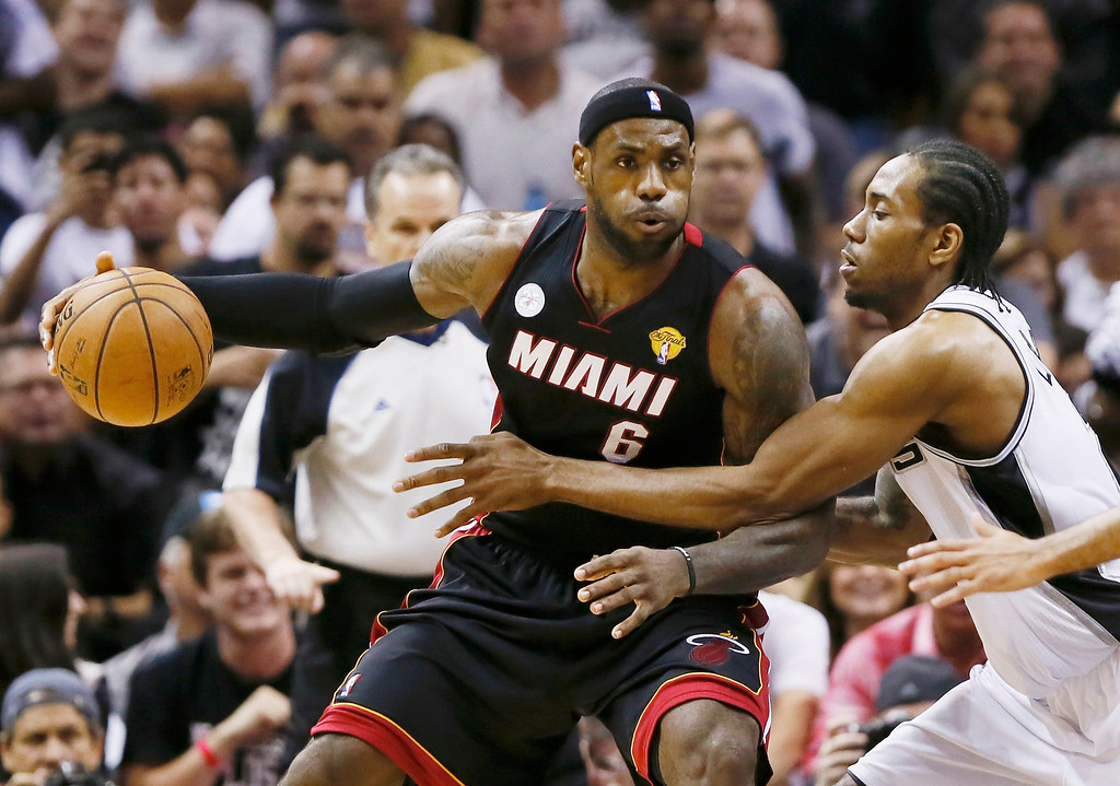 . Miami Heat\'s LeBron James (L) leans into San Antonio Spurs\' Kawhi Leonard during the first quarter in Game 4 of their NBA Finals basketball series in San Antonio, Texas June 13, 2013.  REUTERS/Lucy Nicholson