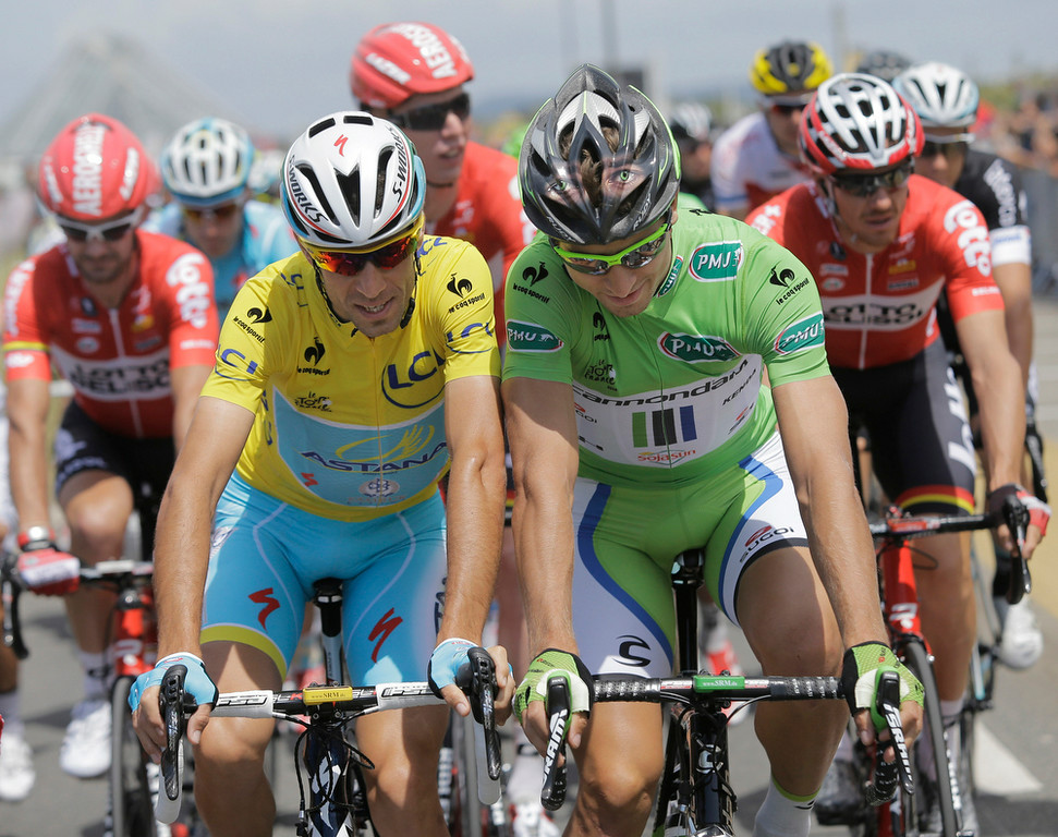. Italy\'s Vincenzo Nibali, wearing the overall leader\'s yellow jersey, and Peter Sagan of Slovakia, wearing the best sprinter\'s green jersey, ride shoulder-to-shoulder during the ceremonial procession prior to the start of the fourth stage of the Tour de France cycling race over 163.5 kilometers (101.6 miles) with start in Le Touquet and finish in Lille, France, Tuesday, July 8, 2014. (AP Photo/Laurent Cipriani)