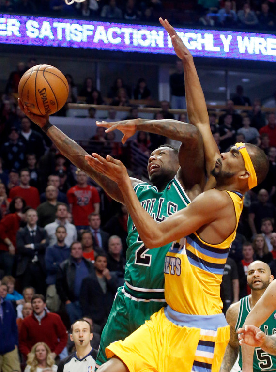 . Chicago Bulls guard Nate Robinson (2) shoots past Denver Nuggets forward Corey Brewer during overtime of an NBA basketball game, Monday, March 18, 2013, in Chicago. The Nuggets won 119-118. (AP Photo/Charles Rex Arbogast)