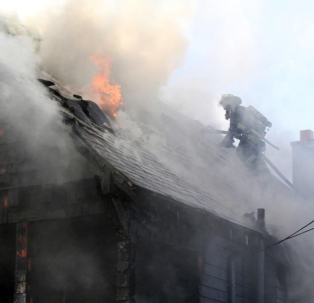 . Oakland firefighters battle a fully involved house fire at a three-story wood-frame house in the 2000 block of East 26th Street in Oakland, Calif., on Tuesday, Jan. 15, 2013.  The owner was not home when the fire started, said Battalion Chief Jenny Ray.(Laura A. Oda/Staff)